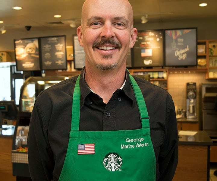 Marine veteran wearing a Starbucks green apron with American flag embroidery